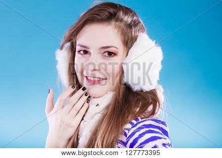 Smiling teenage girl wearing fluffy white earmuff in winter fashion cold time.