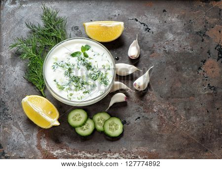 Tzatziki sauce. Fresh dip with herbs dill and mint. Food background