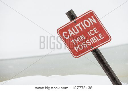Sign warning danger caution about thin ice on frozen lake water