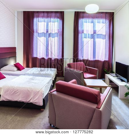 Double hotel room with violet curtains and decorations