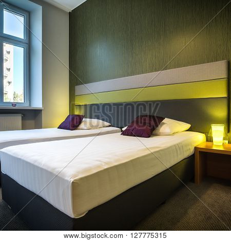 Two neat single beds in green hotel room