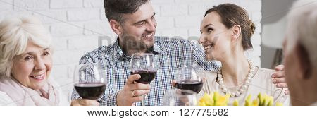 Loving young marriage and their parents celebrating family time during holiday. Drinking a toast with red wine