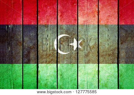 Libya wooden grunge flag. Libya flag painted on the old wooden planks. Vintage retro picture from my collection of flags.