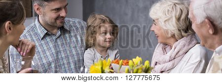 Young marriage with little daughter visiting grandparents during family dinner