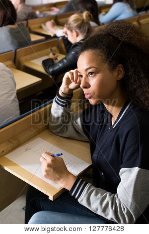 Shot of a student thinking of the answers on her exam