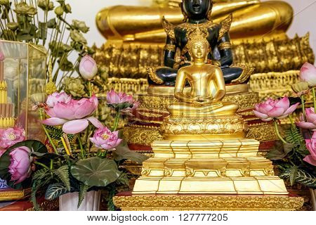 Close Up Of Small Golden Buddha Statue In Lotus Position With Flowers At Wat Pho Bangkok Thailand. Buddhism. Praying Meditation. Religious Buddhist Symbol