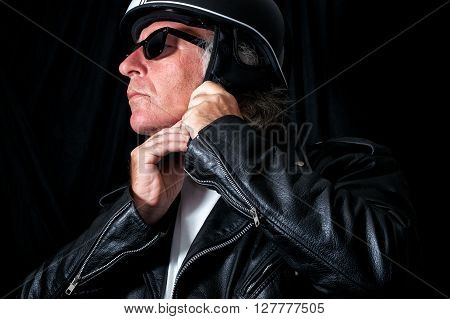 Biker In Leather Jacket And Sunglasses Adjusting Helmet