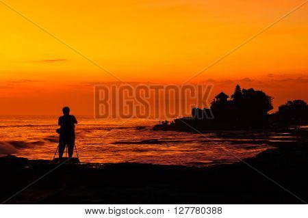 Silhouetted of photographer and Tanah Lot at sunset Bali Indonesia.
