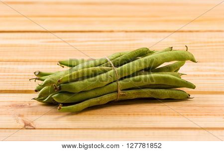 Fresh snow peas isolated on wooden table