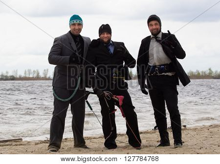 Cherkasy, Ukraine - APRIL 21, 2016: Male office workers in suits ride kites. Business and Sports Festival.