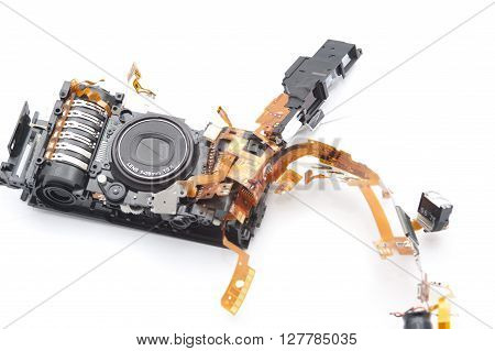Isolated disassembled pocket film camera with exposed printed circuits capacitors and closed lens over white background