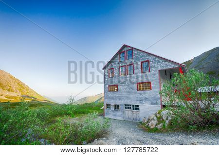 Aging Alaskan gold rush building sits on a ridge over looking the valley near Independence Mine.