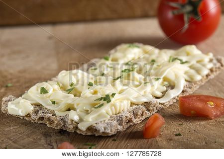 Crispbread with cheese tomato and herbs on wooden background. Healthy breakfast. ** Note: Shallow depth of field