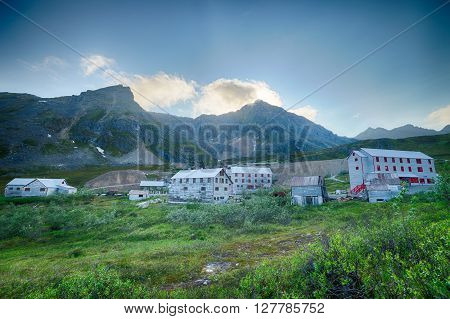 Aging buildings of an Alaskan gold rush town beneath the mountains.