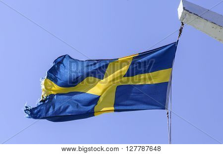Sweden, Swedish Standards. Blue and yellow. On top of a ship. Strong wind, sunny.