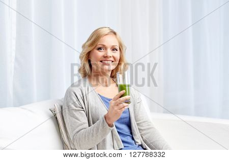healthy eating, vegetarian food, dieting, detox and people concept - smiling middle aged woman drinking green fresh vegetable juice or smoothie from glass at home