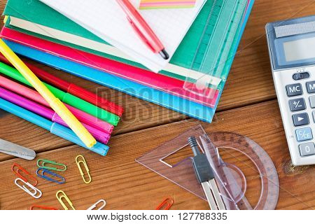 education, school supplies, stationery and object concept - close up of felt pens with clips, notebooks and rulers on wooden table