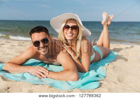 love, travel, tourism, summer and people concept - smiling couple on vacation in swimwear and sunglasses sunbathing on beach