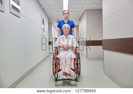 medicine, age, support, health care and people concept - nurse taking senior woman patient in wheelchair at hospital corridor