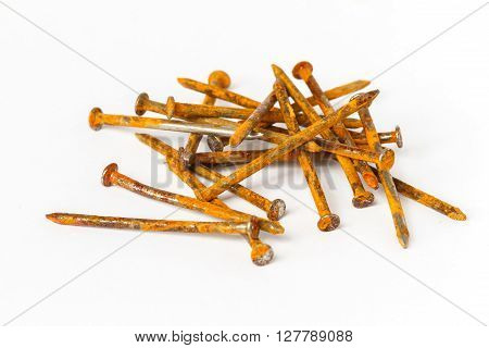 Rusty red nail pile on white background