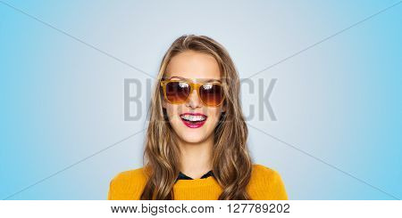 people, style and fashion concept - happy young woman or teen girl face in sunglasses over blue background