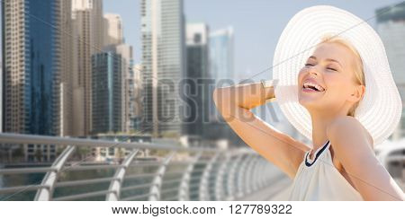 people, summer holidays, travel, tourism and vacation concept - happy beautiful woman in sun hat enjoying summer over dubai city waterfront background