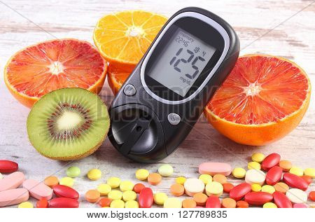 Glucose meter with result of measurement sugar level fresh natural fruits and medical pills tablets and supplements concept of diabetes healthy lifestyle and nutrition
