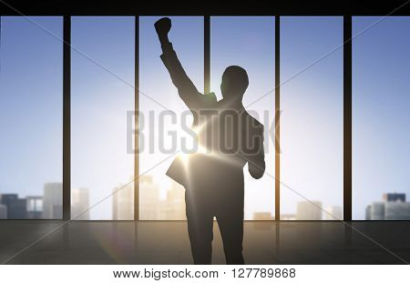 business, success, gesture and people concept - silhouette of happy businessman raising fist and celebrating victory over office window background