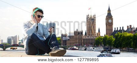 technology, travel, tourism and people concept - smiling young man or teenage boy in headphones with smartphone listening to music over london city and big ben tower background