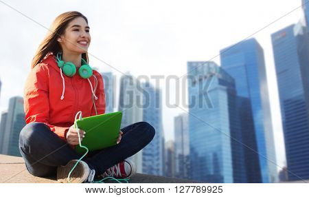 technology, travel, tourism, music and people concept - smiling young woman or teenage girl with tablet pc computer and headphones over singapore city skyscrapers background