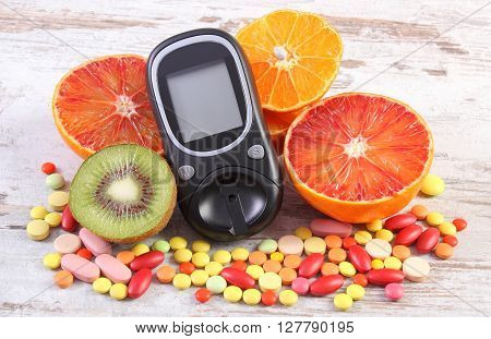 Glucose meter for measurement sugar level fresh natural fruits and medical pills tablets and supplements concept of diabetes healthy lifestyle and nutrition