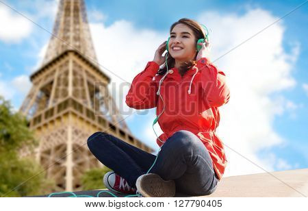 technology, travel, tourism and people concept - smiling young woman or teenage girl in headphones listening to music over paris eiffel tower background