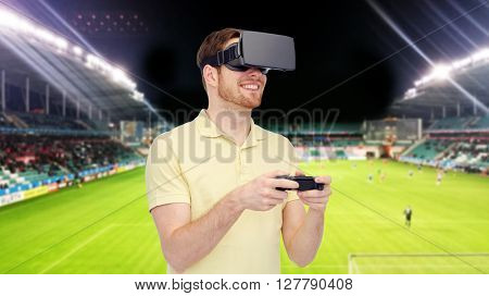 3d technology, virtual reality, sport, entertainment and people concept - man with virtual reality headset or 3d glasses playing with game controller gamepad over football field on stadium background