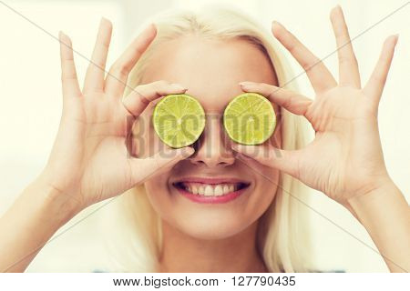 healthy eating, organic food, fruit diet, comic and people concept - happy woman having fun and covering her eyes with lime slices
