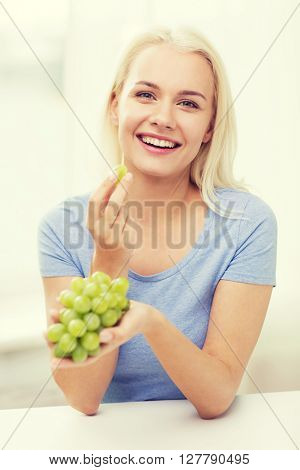 healthy eating, food, fruits, diet and people concept - happy woman eating grapes at home