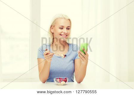 healthy eating, dieting and people concept - smiling young woman with smartphone eating fruit salad at home