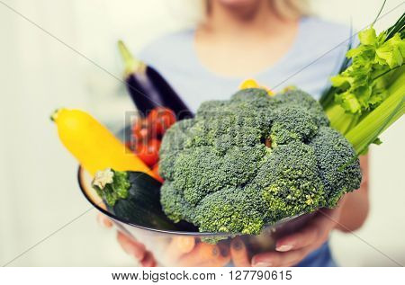 healthy eating, vegetarian food, diet and people concept - close up of woman holding vegetables in bowl