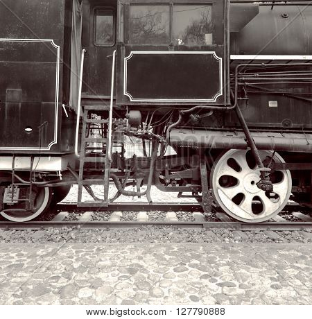 Two train wheels and locomotive driver's cab of an old steam locomotive