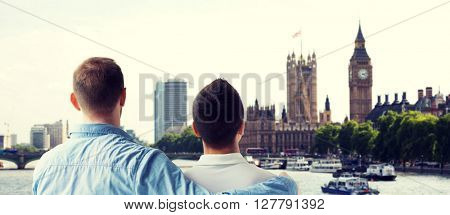 people, homosexuality, same-sex marriage, travel and love concept - close up of happy male gay couple hugging from back over big ben and houses of parliament in london background