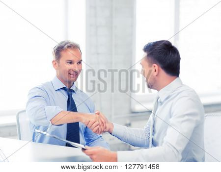 picture of businessmen shaking hands in office