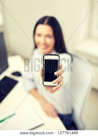 business, education, technology and people concept - close up of happy woman showing smartphone blank screen at office