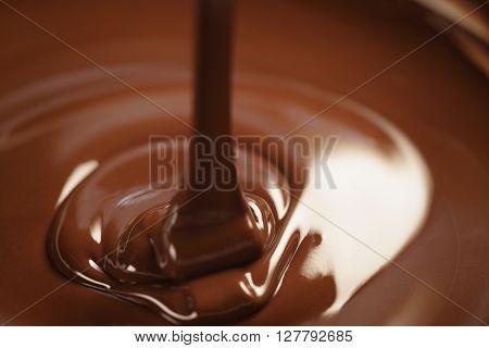 melted dark chocolate flows closeup, shallow focus