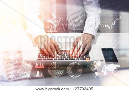 Business charts and male hands using laptop placed on desktop with smartphone. Double exposure