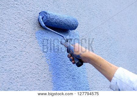 workman painting the wall with paint roller