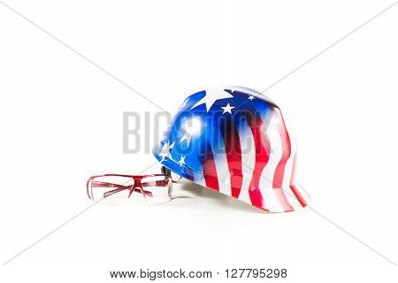 Safety items for construction sites. American helmet with color flag and safety glasses on white background.