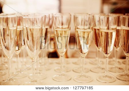 Rows of Champagne Glasses Served on Event. Image Toned with Gold Colors. Selective Focus.