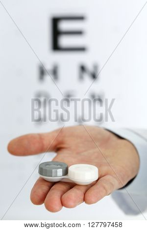 Male Doctor Hands Giving Pair Of Contact Lens
