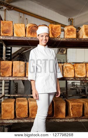 Smiling Female Baker Standing Against Freshly Baked Breads