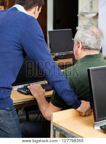 Teacher Assisting Senior Man At Computer Desk