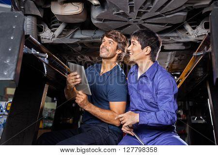Mechanics With Digital Tablet Examining Underneath Car